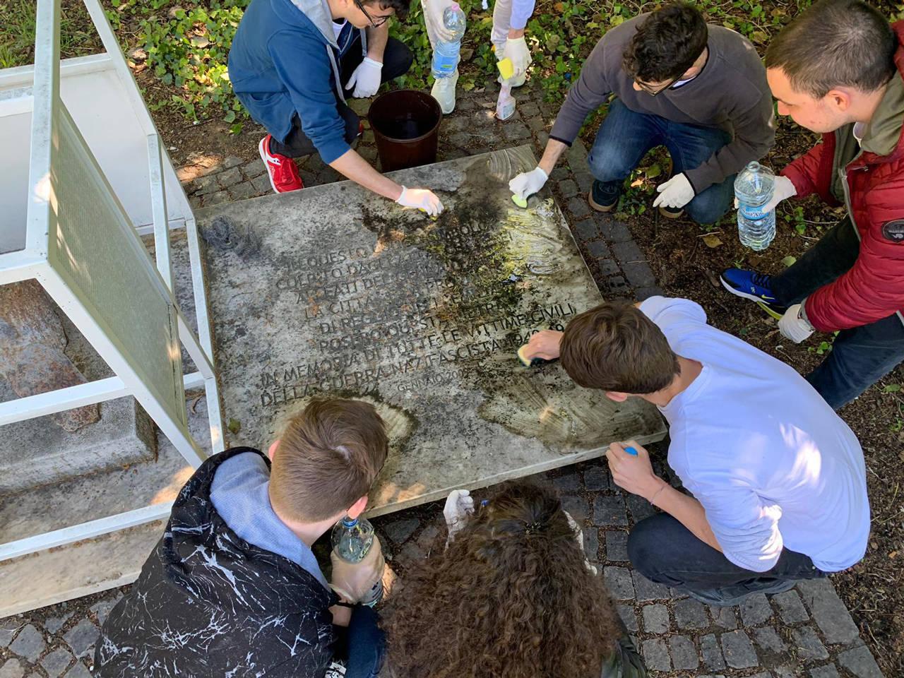 studenti puliscono monumento